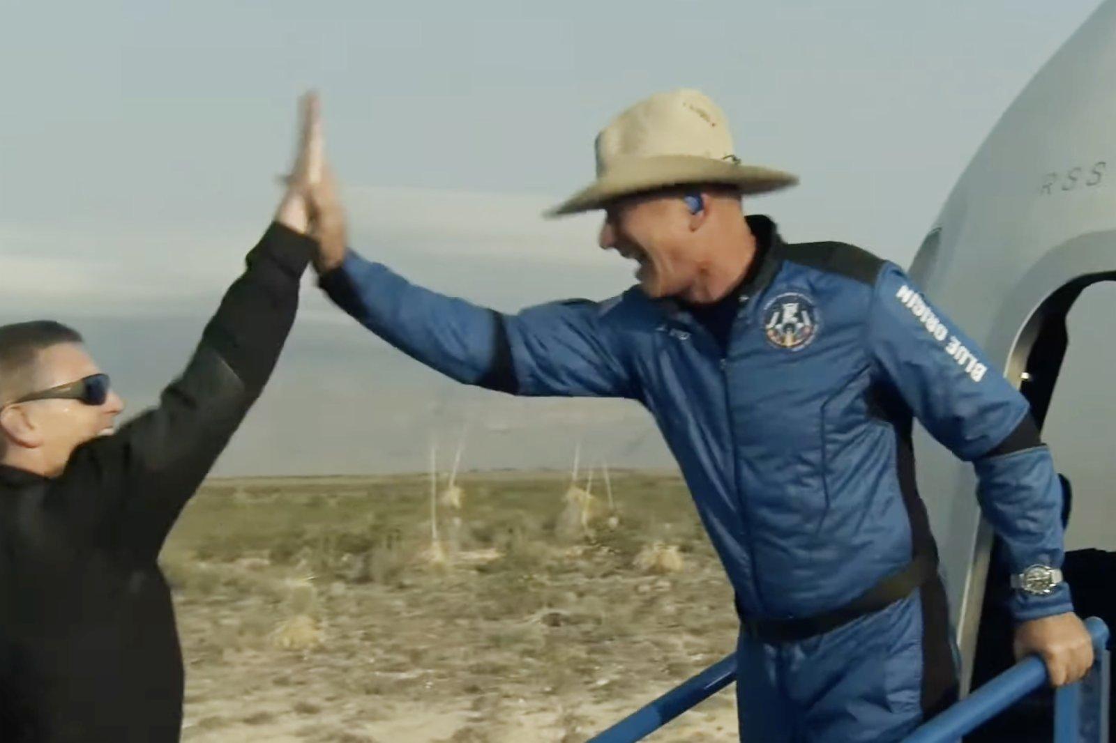 這張美國藍色起源公司7月20日發布的視頻截圖顯示,「新謝潑德」飛行器在美國得克薩斯州西部着陸後,該公司創始人傑夫·貝索斯(右)走出飛行器慶祝。新華社發(藍色起源公司供圖)