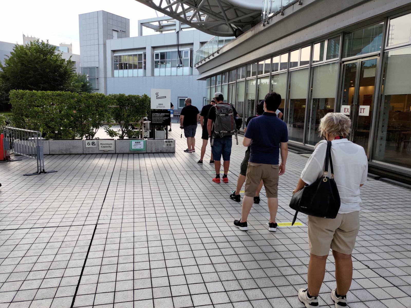 傳媒中心場館外設有專門吸煙區,長期有記者在外排隊。(大公報記者 張銳 攝)