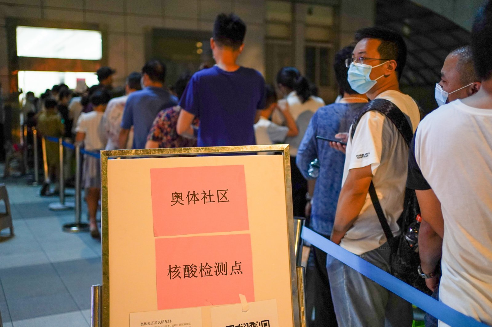 7月21日晚,在南京市建鄴區一處檢測點,市民在排隊準備進行核酸檢測。(新華社)
