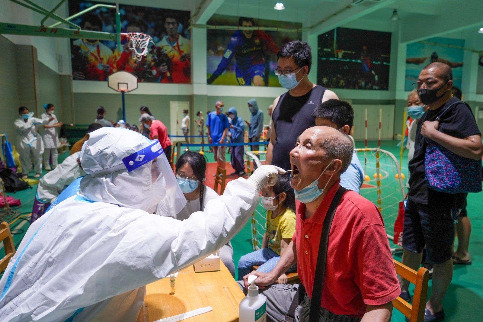 7月21日晚,在南京市建鄴區一處檢測點,醫務人員在為市民進行核酸檢測取樣。(新華社)
