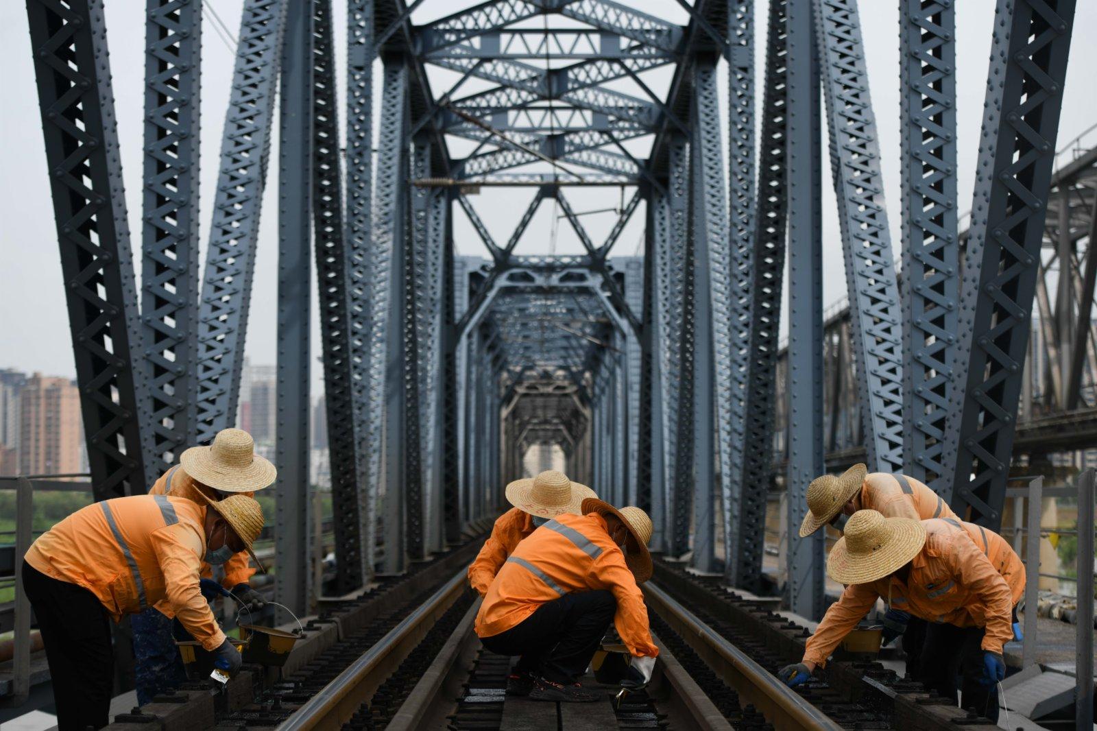 7月21日,橋隧工在蚌埠淮河鐵路大橋上進行軌距測量。(新華社)