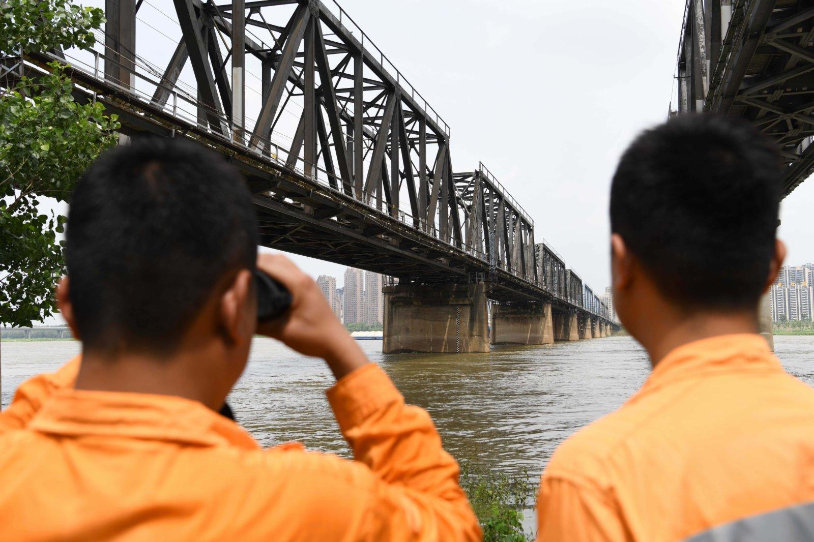 7月21日,橋隧工在觀測蚌埠淮河鐵路大橋下的淮河水位。(新華社)