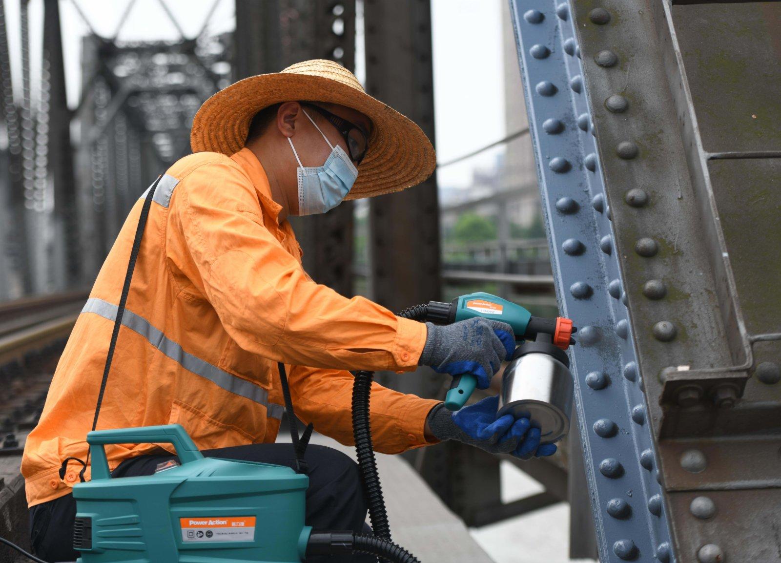 7月21日,橋隧工倪國龍在蚌埠淮河鐵路大橋上進行噴漆作業。(新華社)