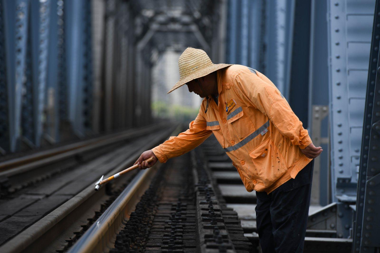 7月20日,橋隧工張道忠在蚌埠淮河鐵路大橋上檢查螺栓。(新華社)