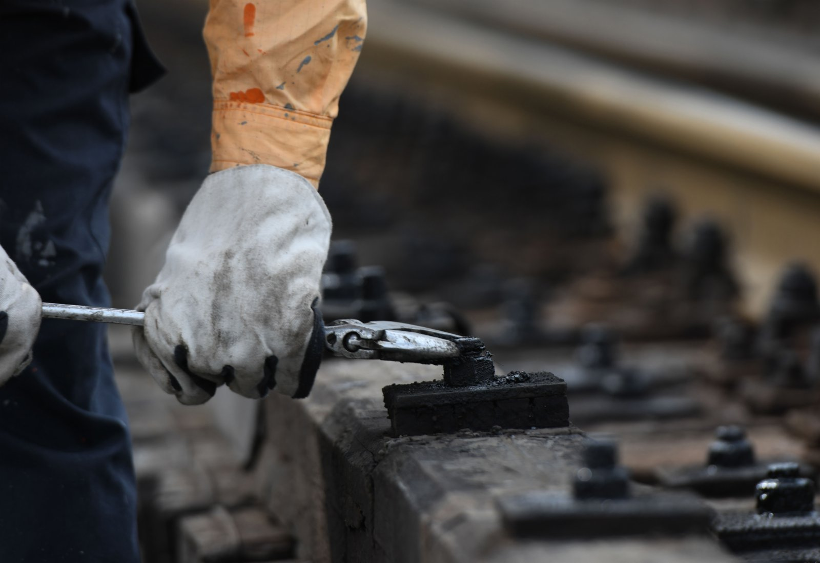 7月21日,一名橋隧工在蚌埠淮河鐵路大橋上進行護木螺栓復緊。(新華社)