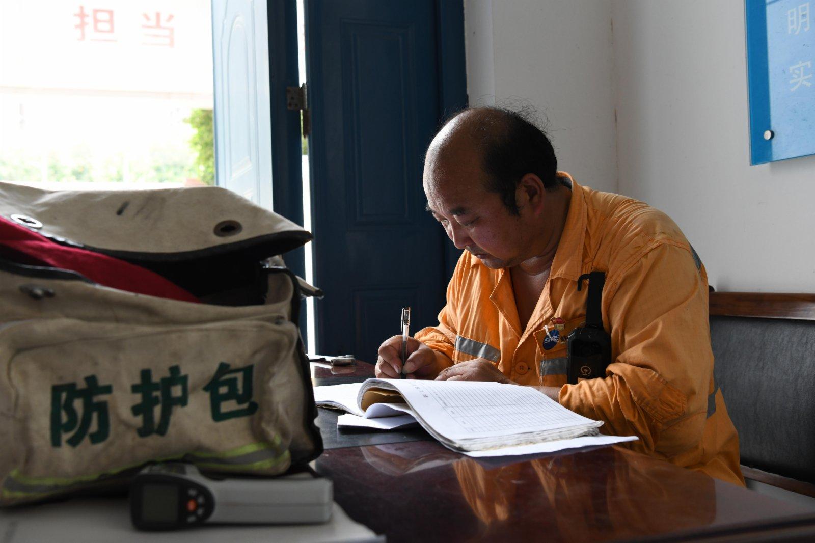 7月21日,橋隧工張道忠在蚌埠工務段蚌埠橋梁車間進行考勤記錄。(新華社)