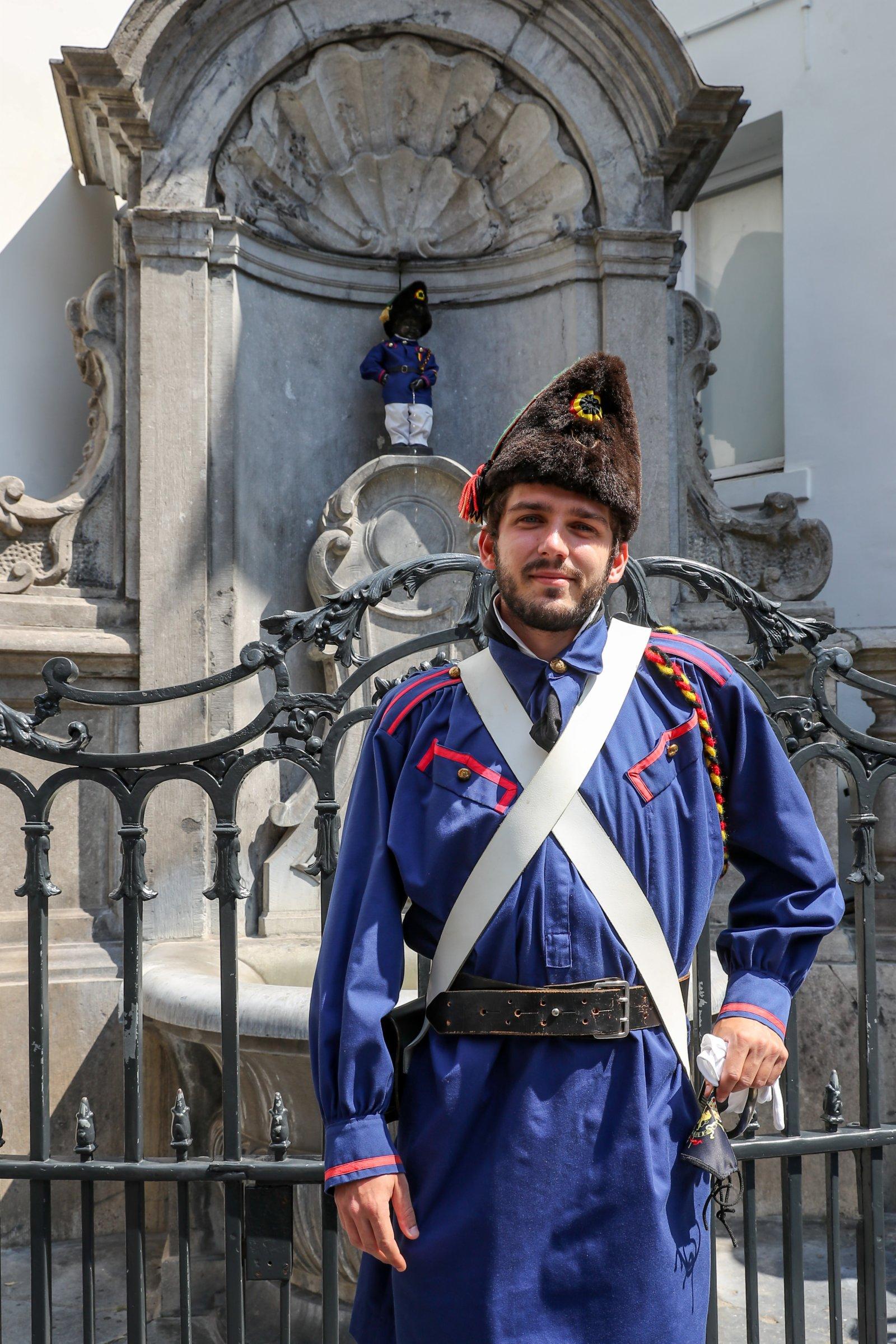 7月21日,一名身穿比利時獨立戰爭志願軍服裝的男子在比利時布魯塞爾與小尿童雕像合影。(新華社)