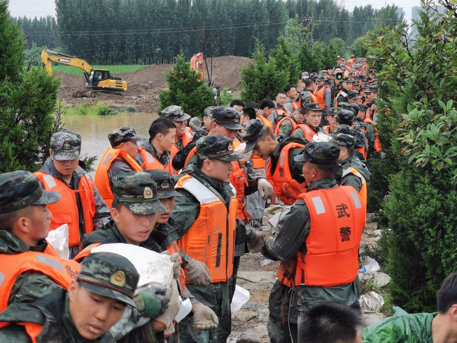 7月21日,武警河南總隊新鄉支隊官兵在新鄉市共產主義渠獲嘉段搬運沙袋封堵管涌。(新華社)