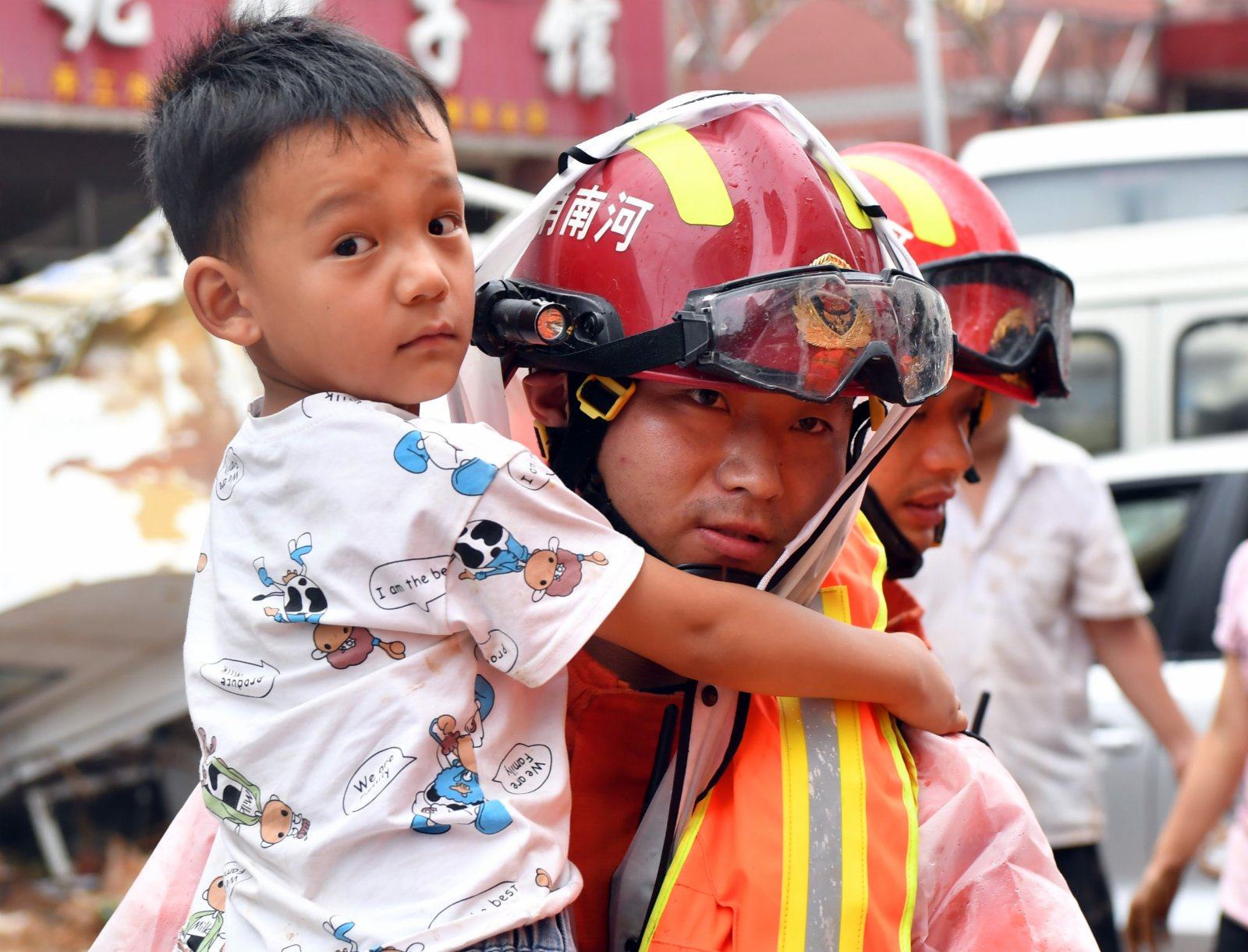 7月21日,在鞏義市米河鎮,消防救援人員幫助群眾轉移。(新華社)