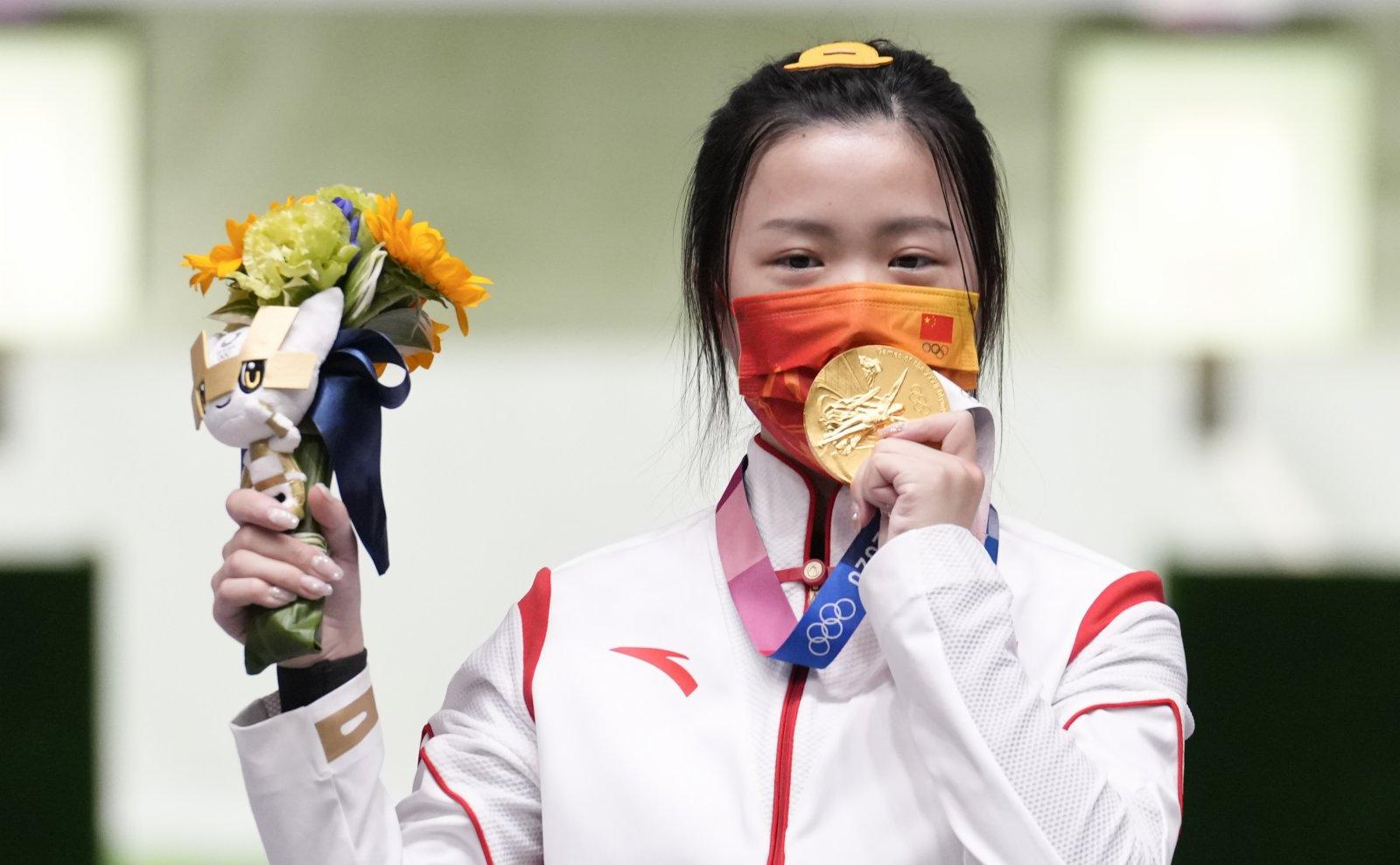 圖為楊倩在頒獎儀式上隔着口罩親吻奧運金牌。(中新社)