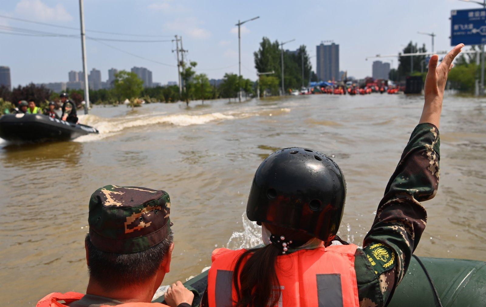 圖為佛山南獅退役軍人志願救援隊的一名隊員為衝鋒舟指揮方向。