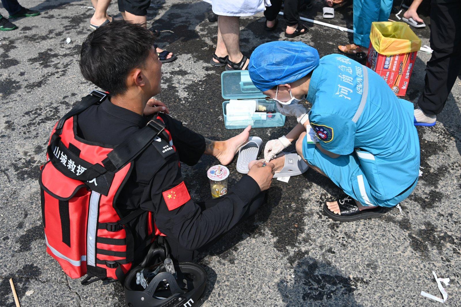 醫務人員在小朱莊救援現場為一名救援隊員清理腳部傷口。