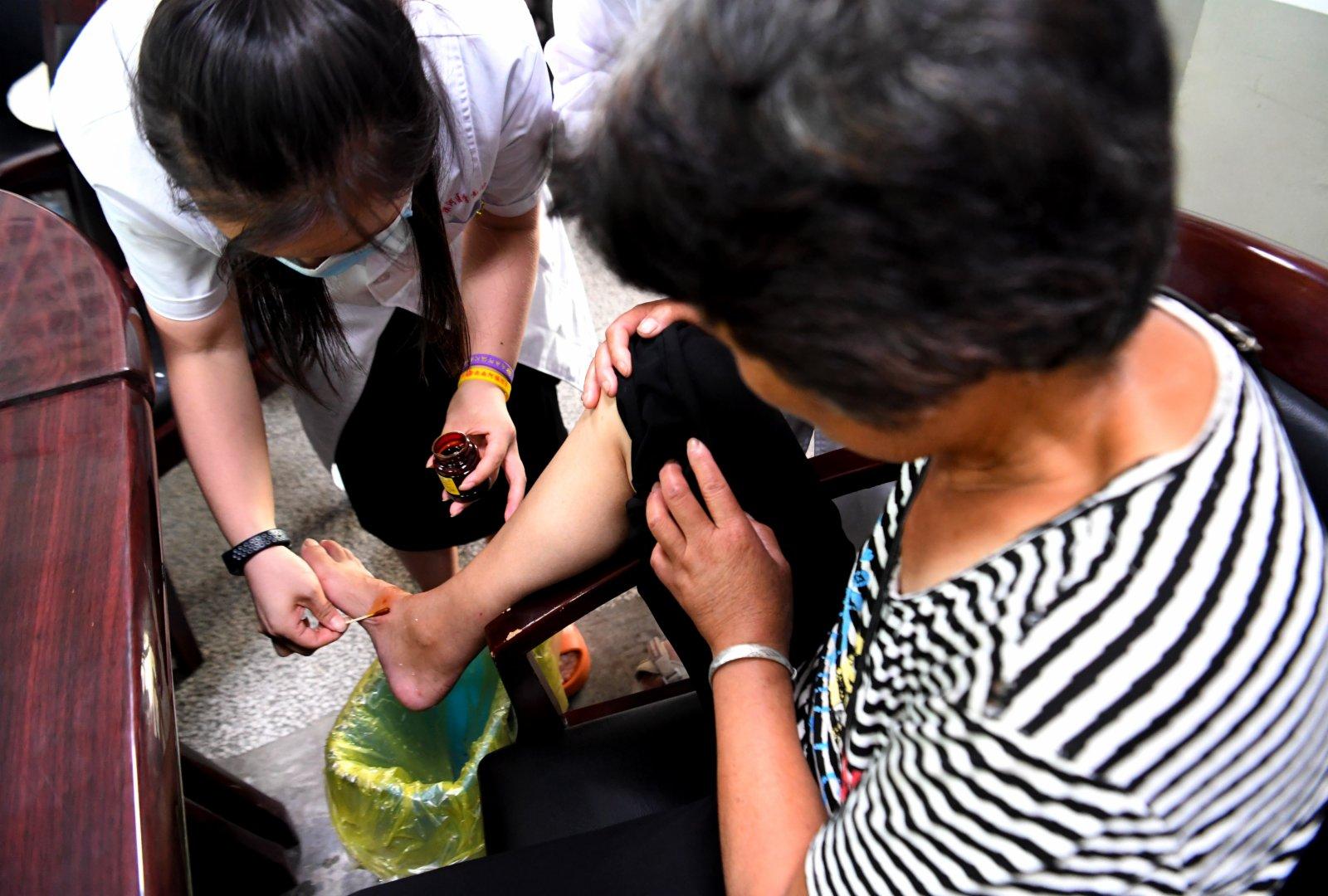 醫護人員在河南省新鄉市第二中學臨時醫療救助點為轉移村民處理傷口。