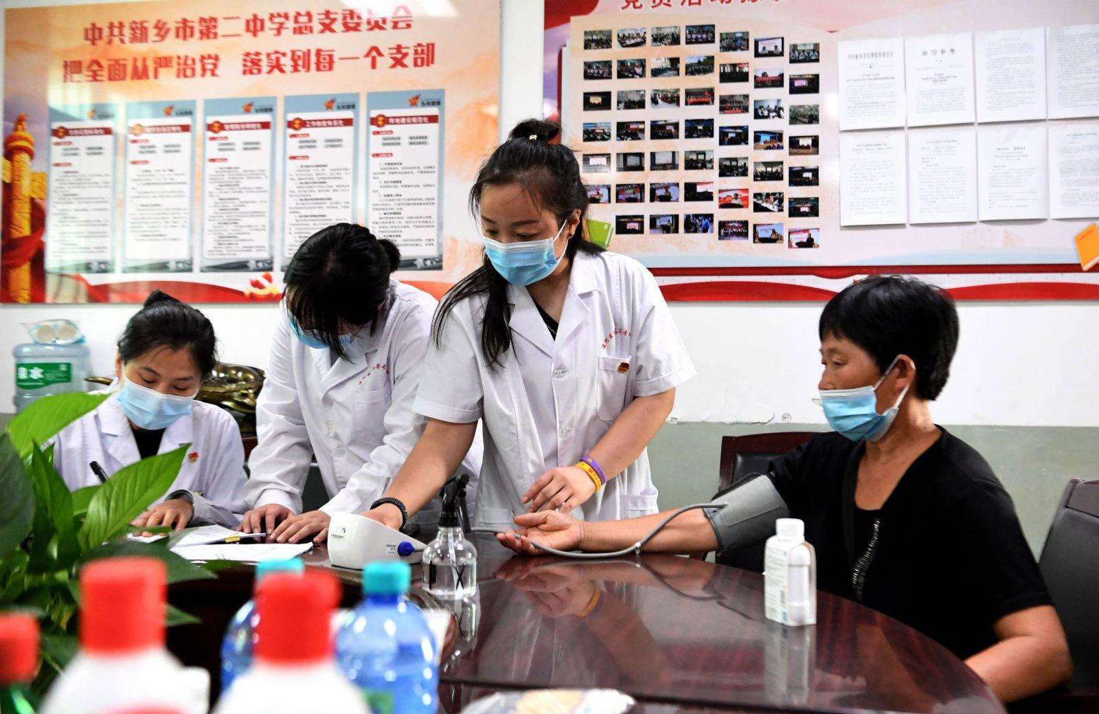 醫護人員在河南省新鄉市第二中學臨時醫療救助點為轉移村民測量血壓。