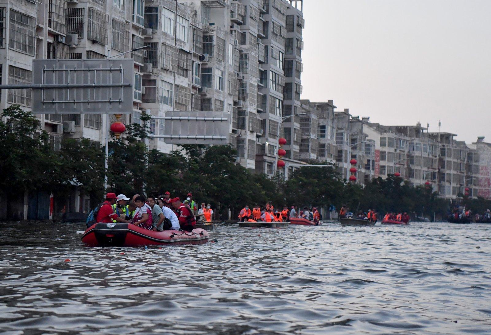 在河南省衛輝市,受困群眾乘坐救援船隻轉移。