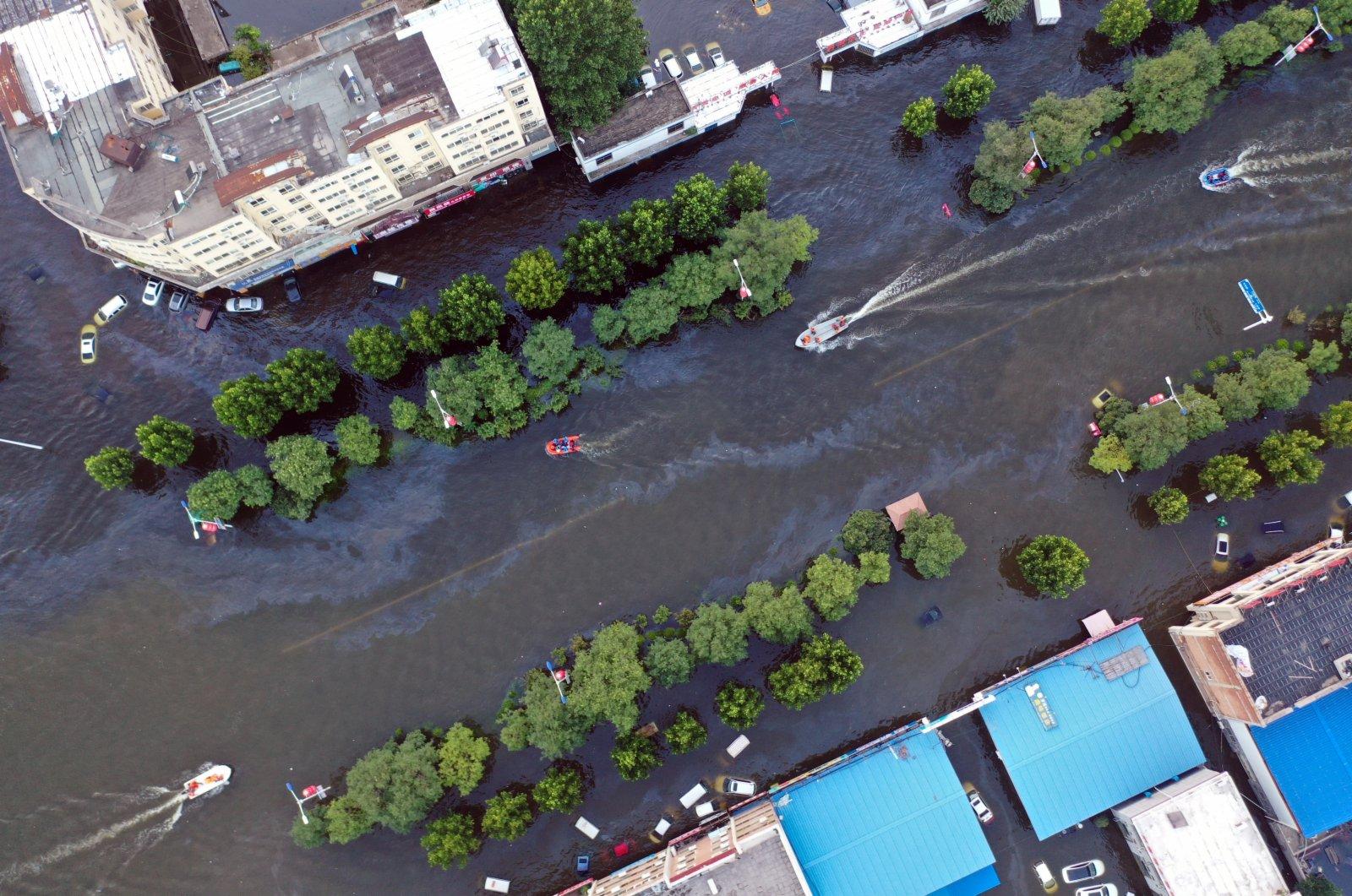 在河南省衛輝市,救援船隻穿梭於城區內。