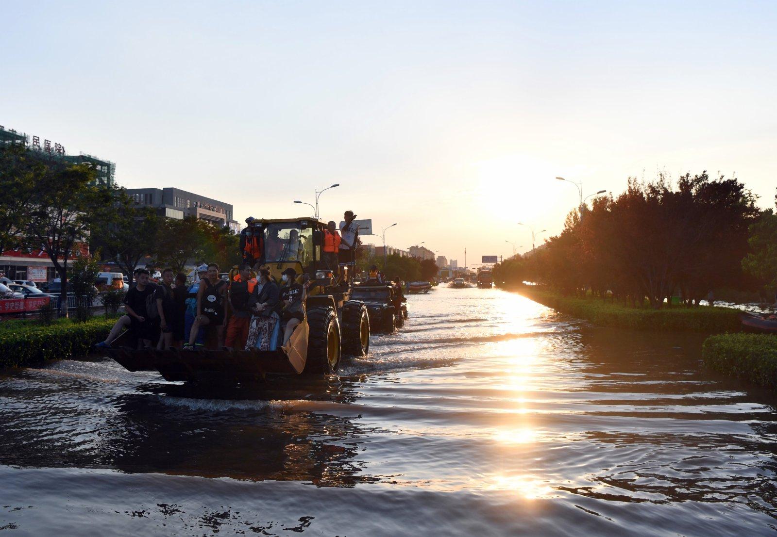 在河南省衛輝市,受困群眾乘坐鏟車轉移。