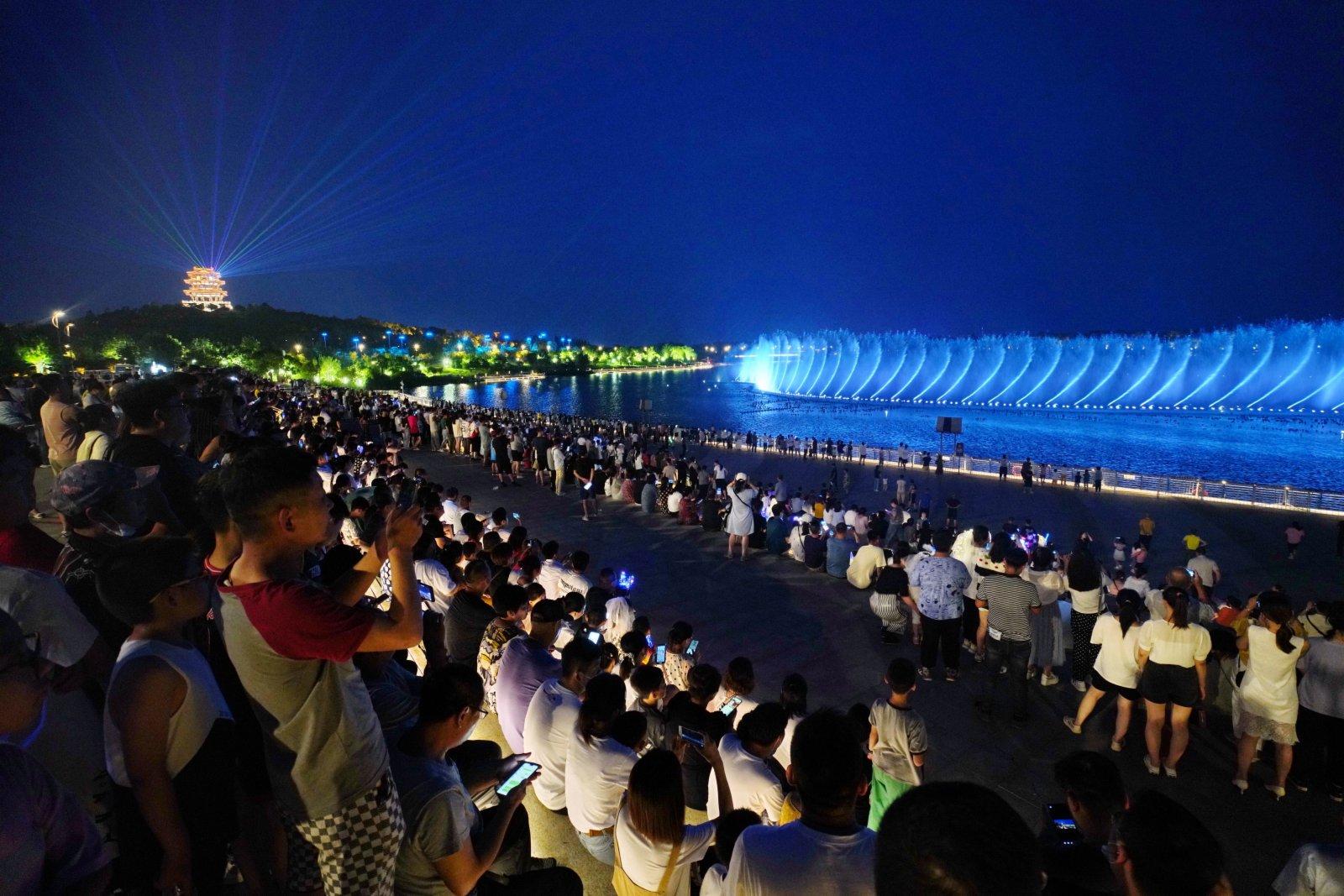 7月26日,遊客在唐山南湖公園內觀看噴泉燈光秀。 新華社
