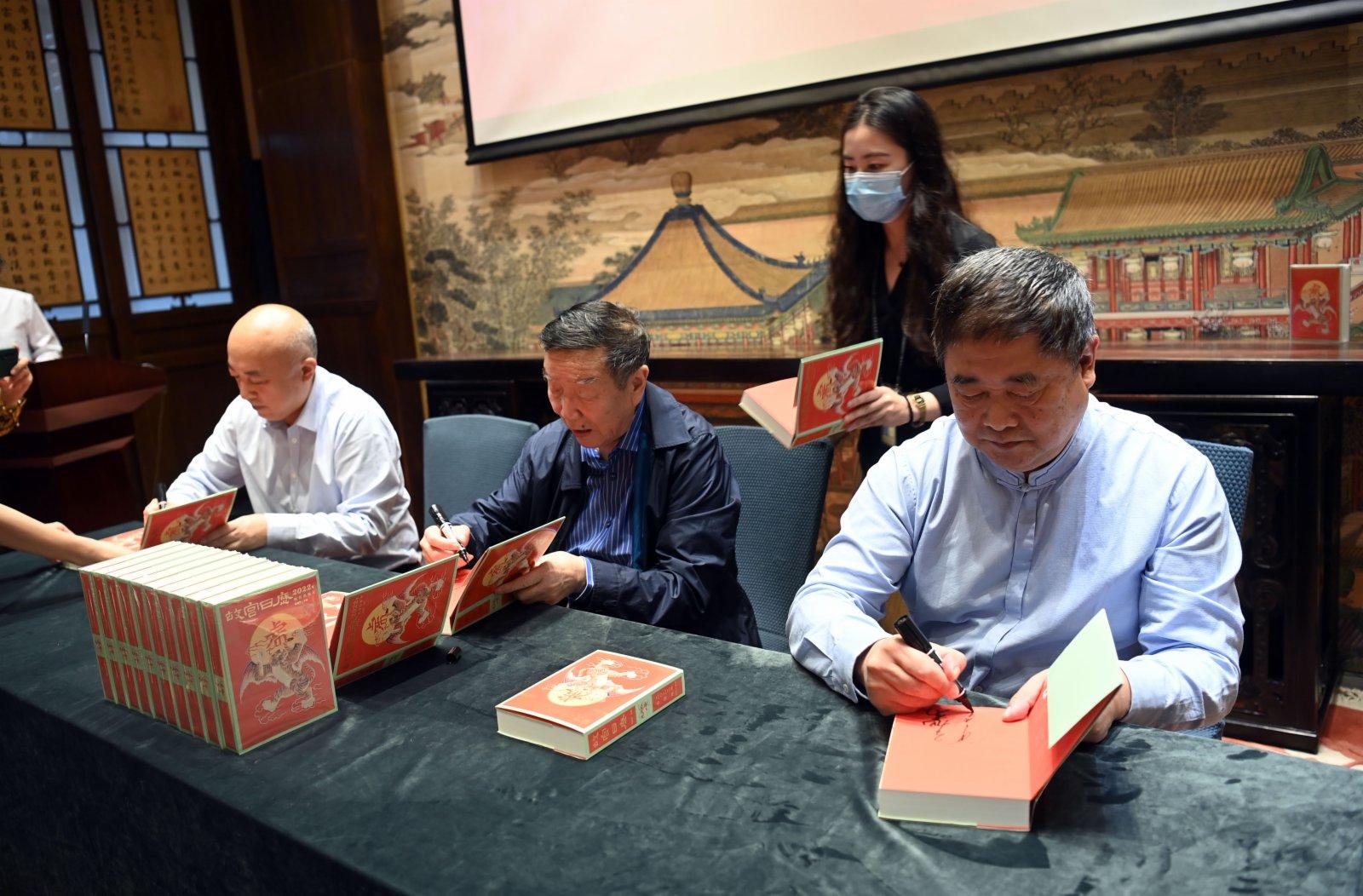 9月6日,故宮博物院院長王旭東(左一),故宮博物院原院長鄭欣淼(左二)、故宮博物院原院長單霽翔(右一)在2022年《故宮日曆》上簽名。