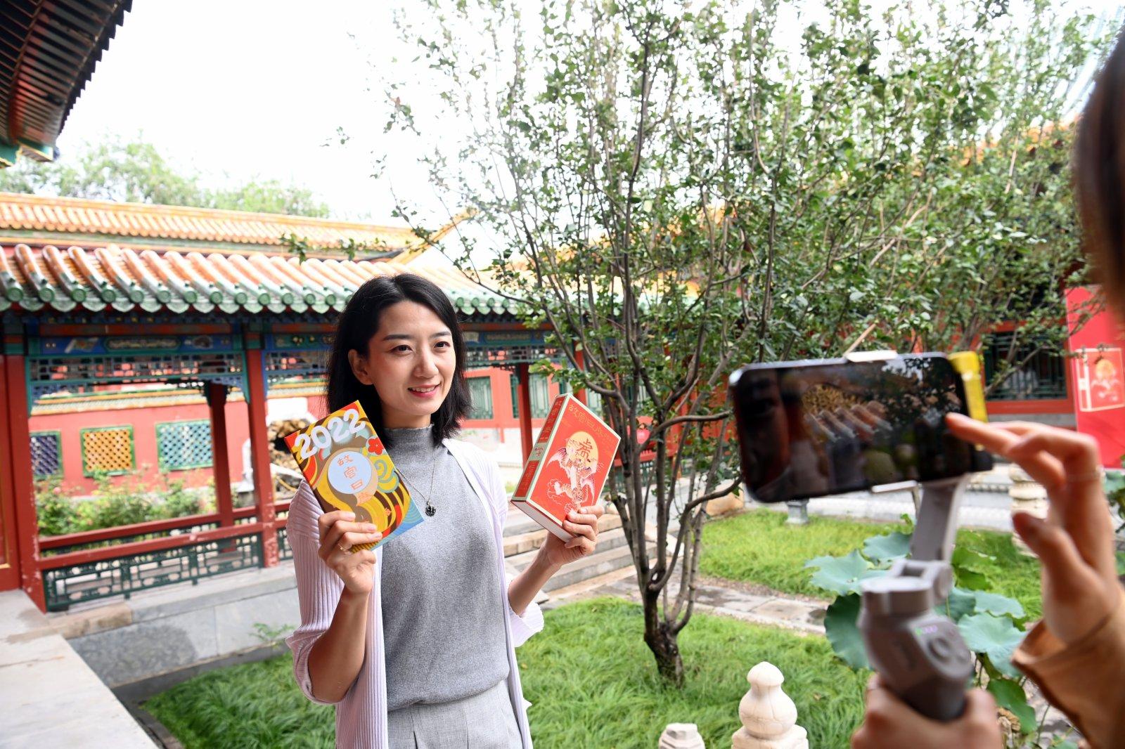 9月6日,一名記者在鏡頭前展示2022年《故宮日曆》。