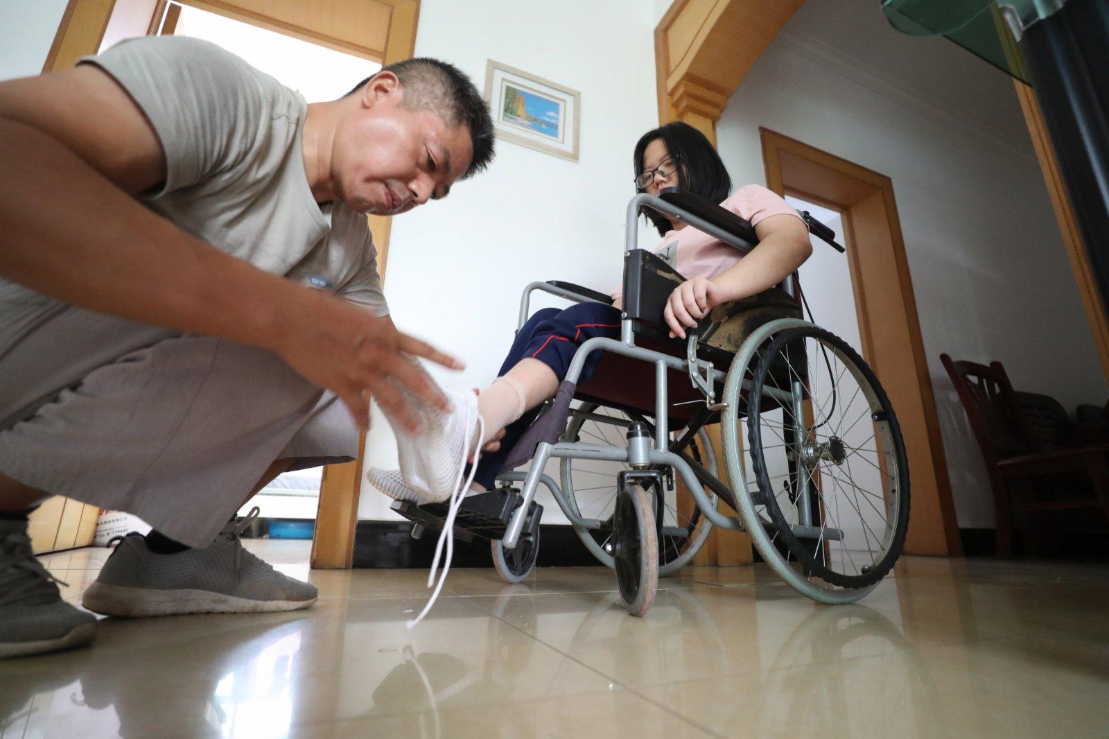 9月1日,謝培軍在家中幫女兒穿好鞋子,準備趕往學校報到。(新華社)