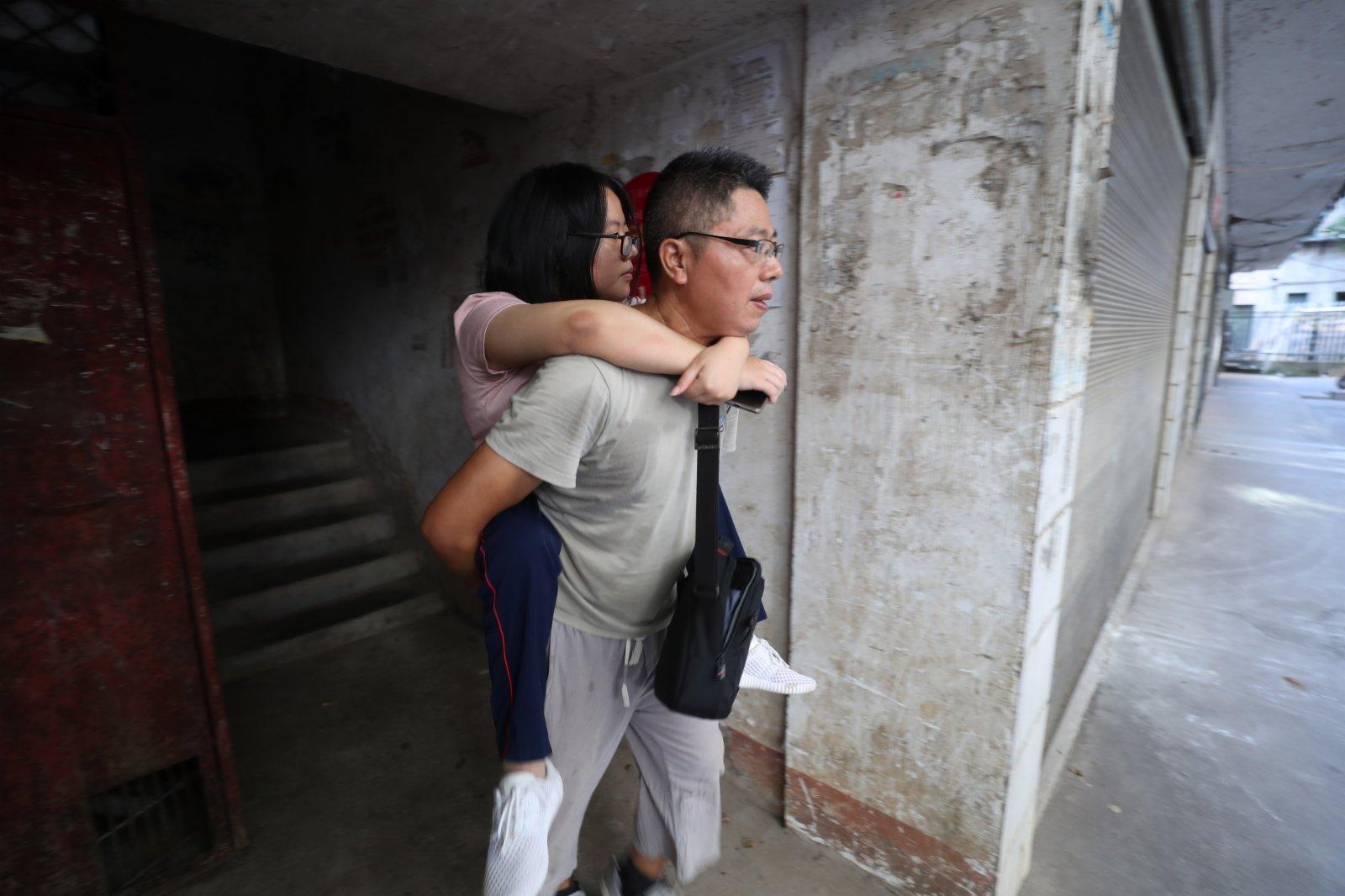 9月1日,謝培軍背女兒出門,準備趕往學校報到。(新華社)