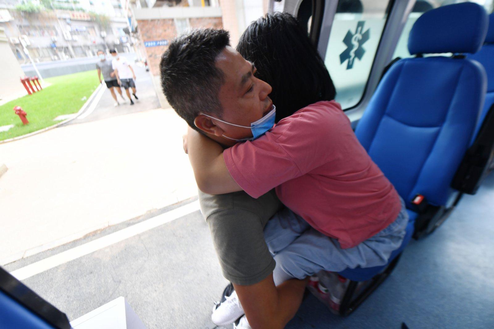 9月2日,謝培軍將女兒從車上抱出來。(新華社)