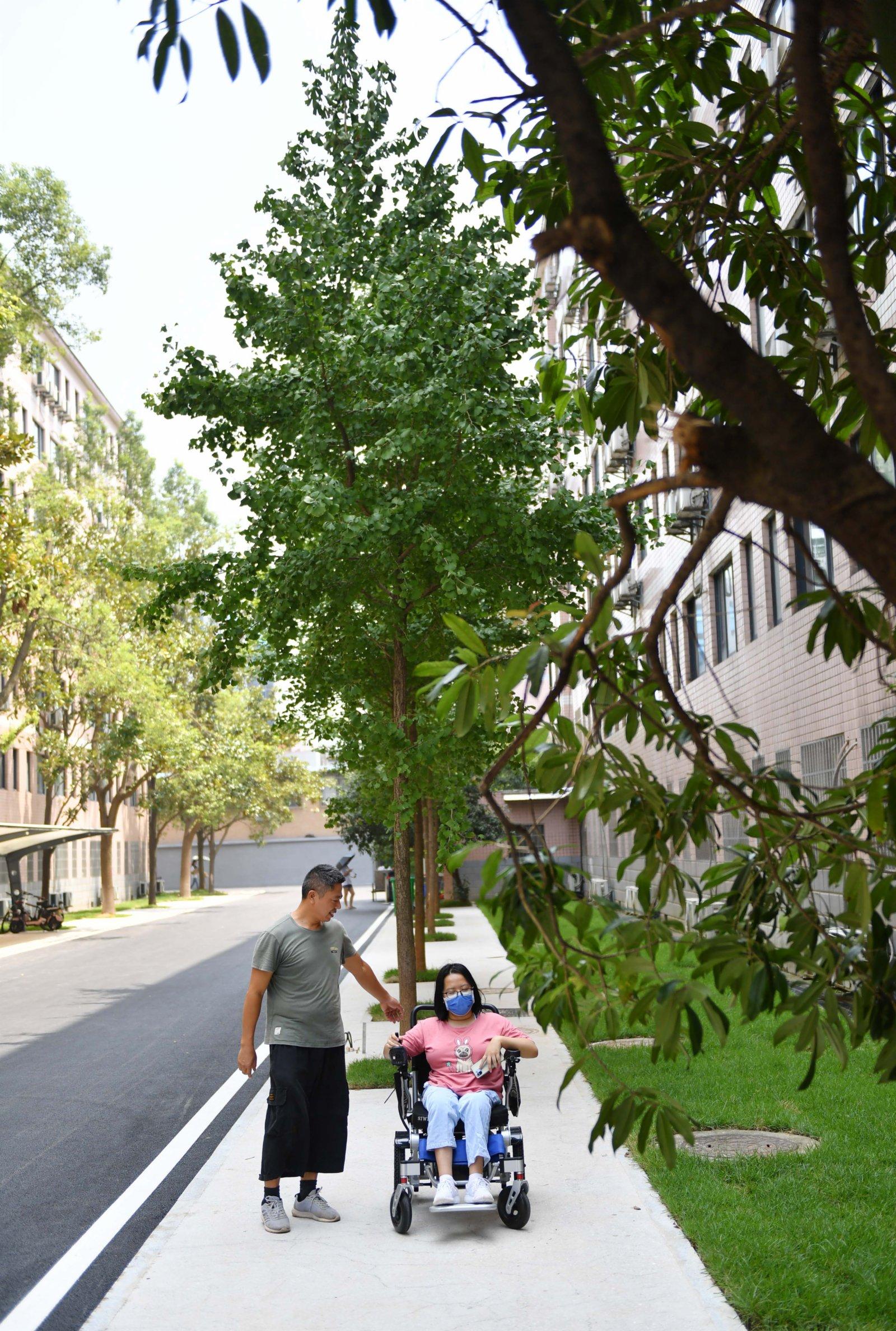 9月2日,謝培軍、謝可欣父女二人在校園中散步。(新華社)