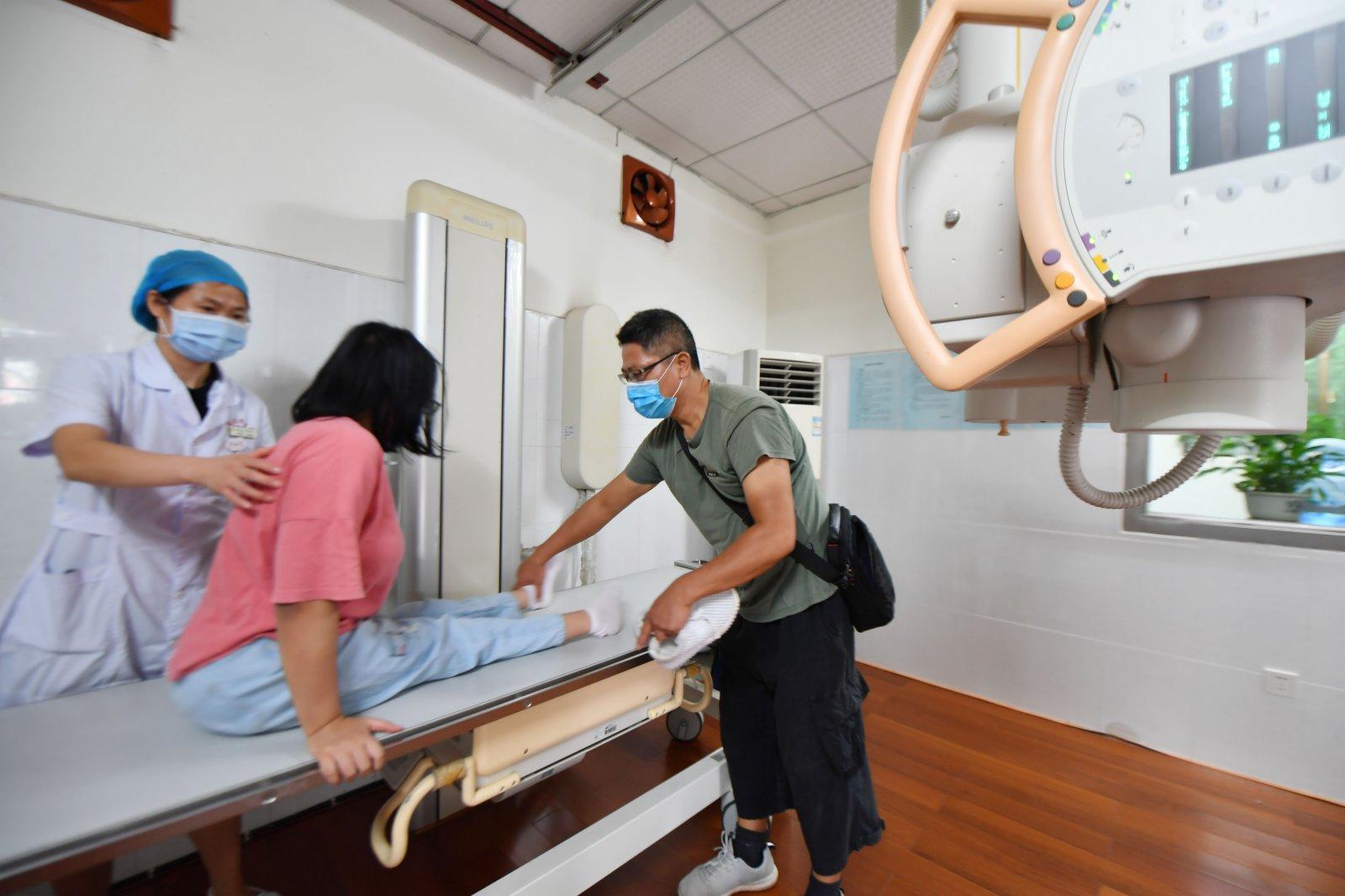 9月2日,謝培軍陪伴女兒在湖南大學校醫院做體檢。(新華社)