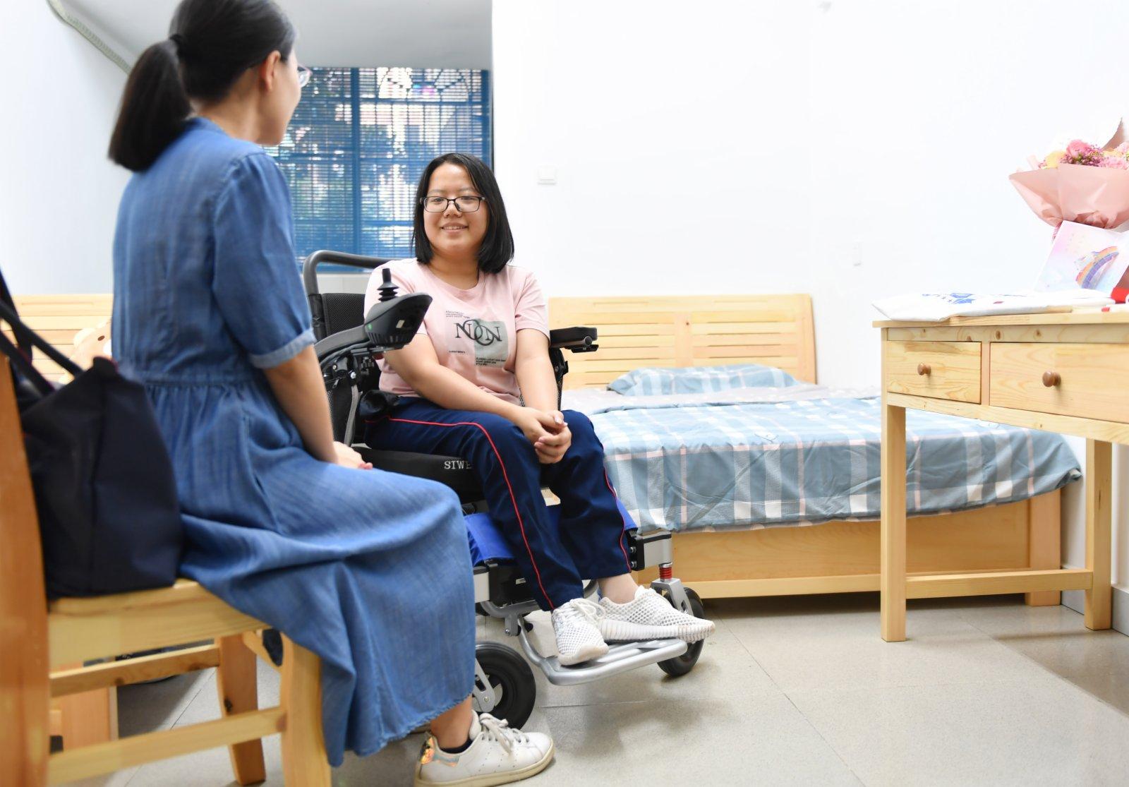 9月1日,謝可欣(右)在宿舍與前來看望她的老師交談。(新華社)
