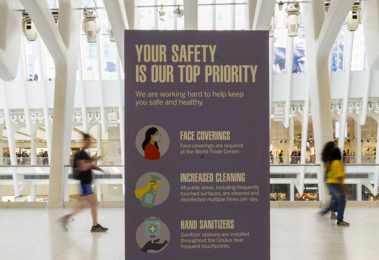 9月6日,人們走過美國紐約世貿中心車站內的防疫提示牌。(新華社)