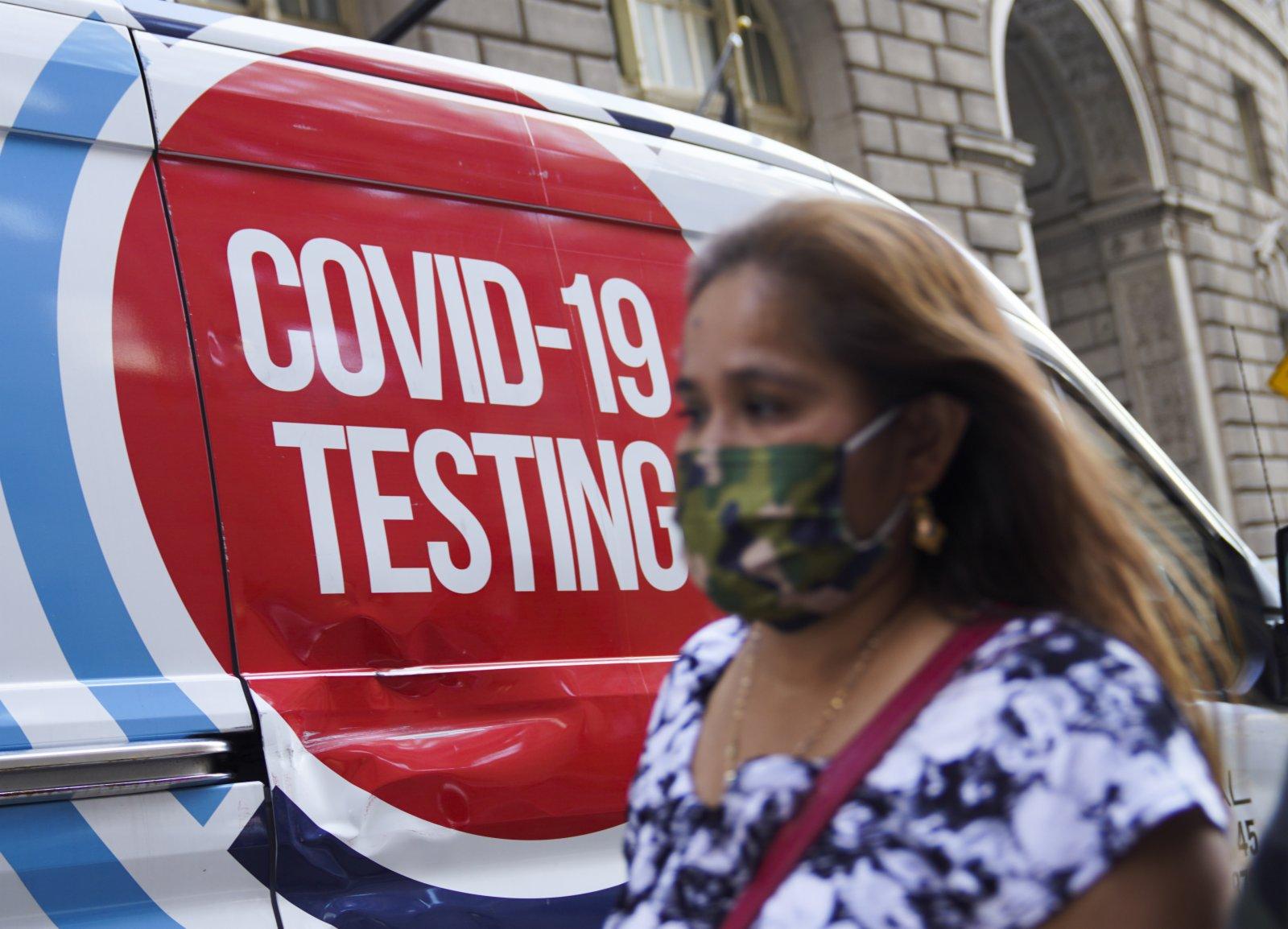 9月6日,一名女子從美國紐約的移動新冠檢測點旁經過。(新華社)