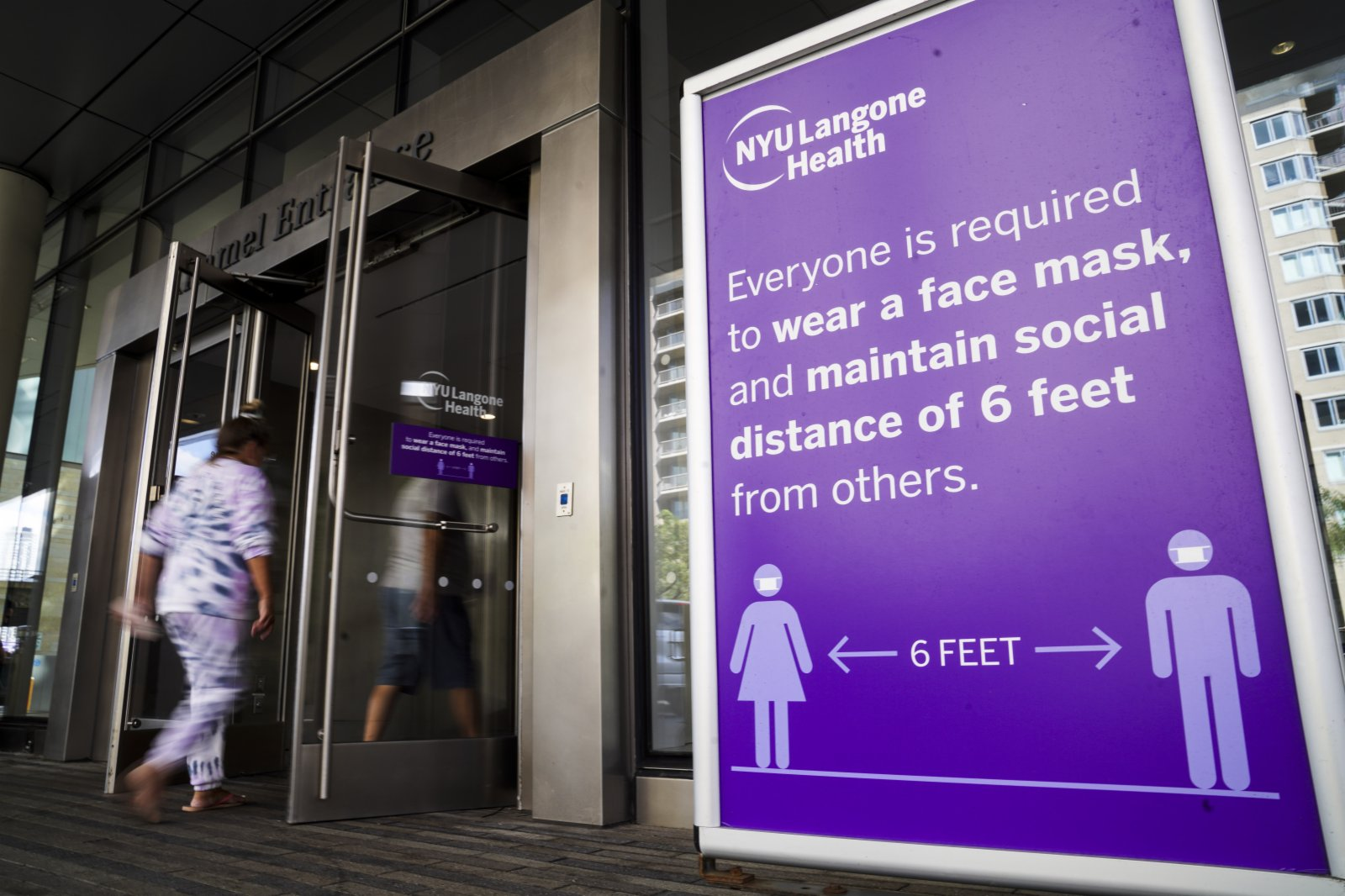 9月6日,人們走過美國紐約一家醫院的防疫提示牌。(新華社)