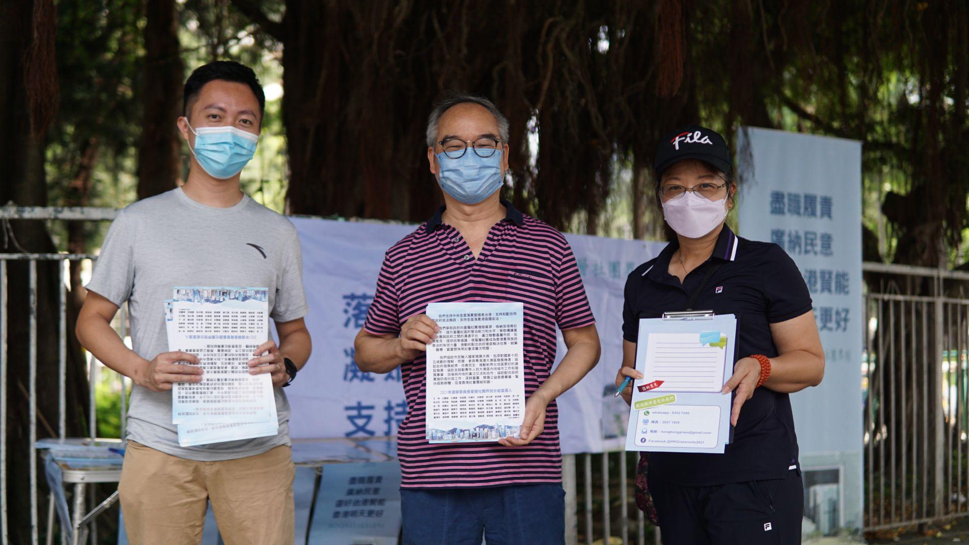 基層社團界別分組選委李梓敬(左一)、前民政事務局局長劉江華(左二)在大圍金獅花園對開街站。