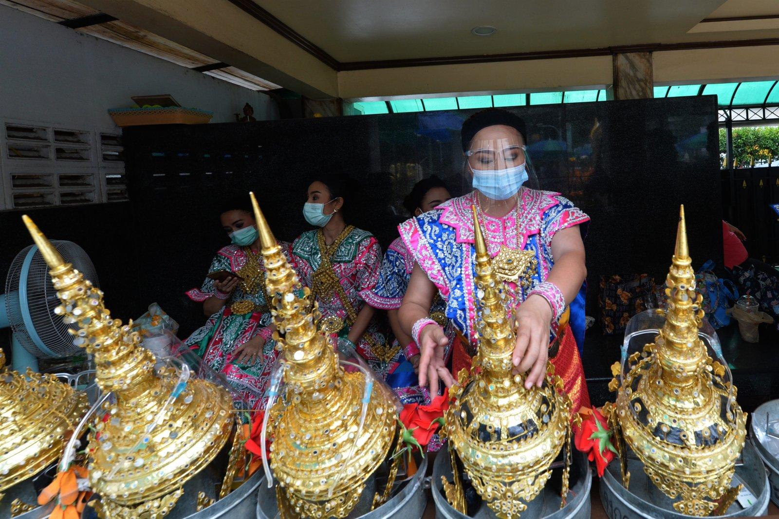 9月11日,在泰國曼谷,佩戴防護面罩的舞者表演完畢後休息。(新華社)