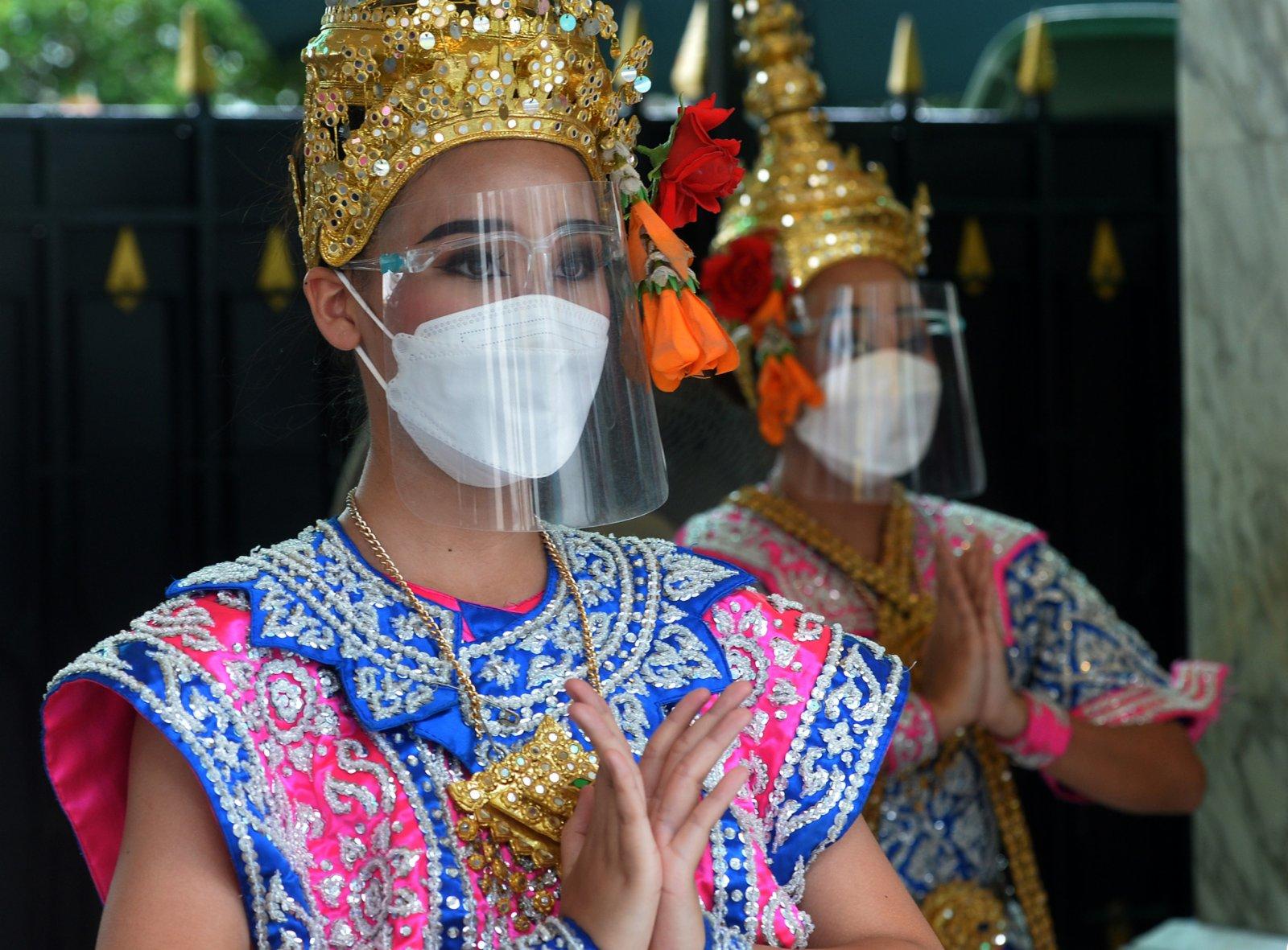9月11日,佩戴防護面罩的舞者在泰國曼谷四面佛表演舞蹈。(新華社)