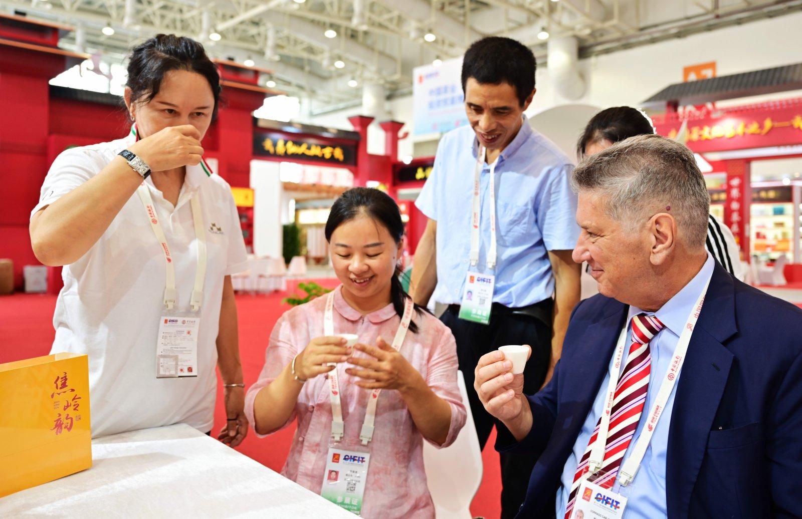在第二十一屆中國國際投資貿易洽談會的中國茶業投資貿易博覽會現場,來自意大利馬爾凱大區蒙卡洛集團的葡萄酒客商(右一)在品嘗武夷山的參展商林麗英(左二)的岩茶。(新華社)