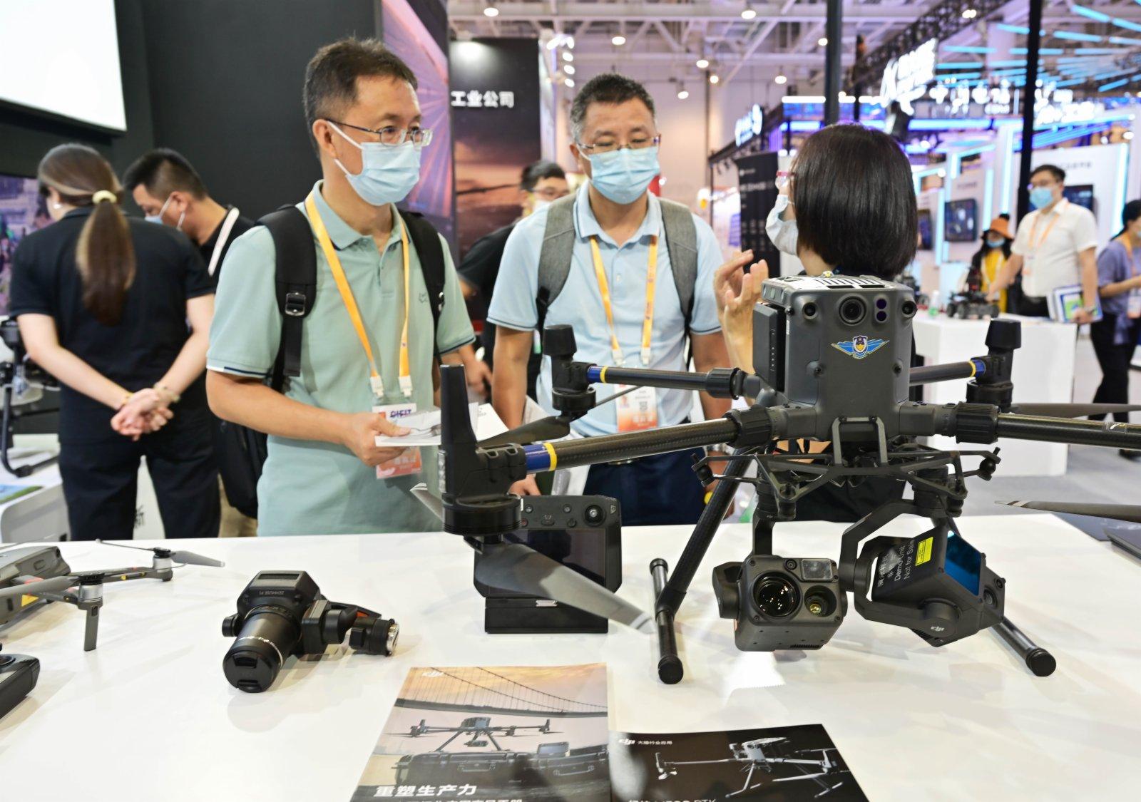 在第二十一屆中國國際投資貿易洽談會展館現場,兩名客商在大疆無人機展台前了解機器的性能。(新華社)