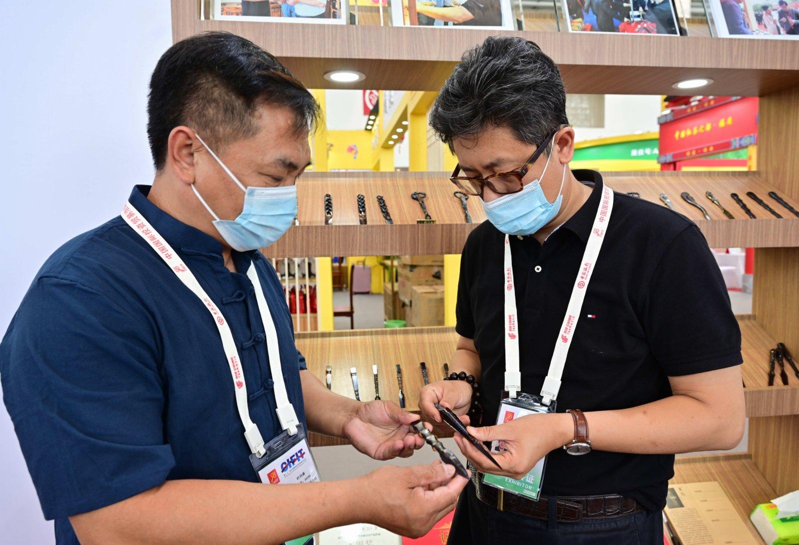 在第二十一屆中國國際投資貿易洽談會展館現場,與會客商(右)在了解福建省南平市松溪縣的非遺傳統手工刀具技藝。(新華社)