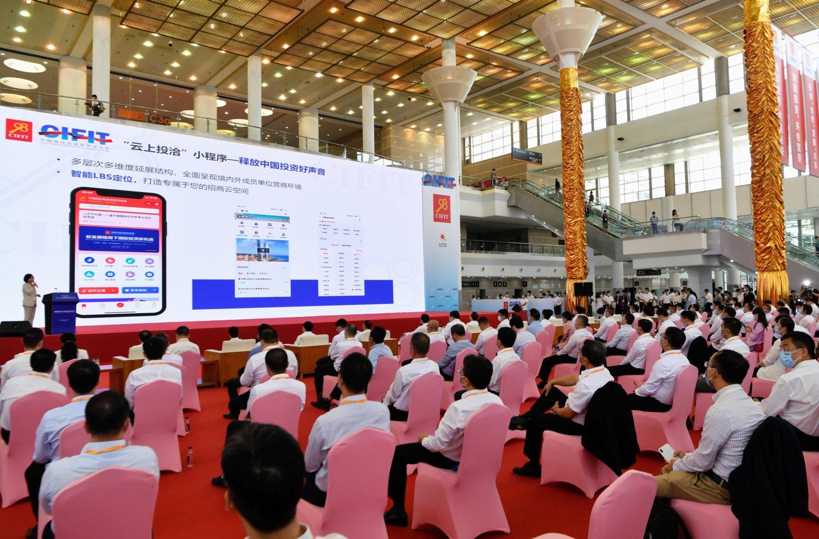 在第二十一屆中國國際投資貿易洽談會展館現場,與會嘉賓在了解「雲上投洽」程序,通過雲上進行投資貿易。(新華社)