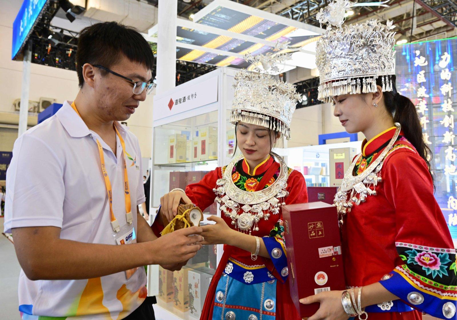 在第二十一屆中國國際投資貿易洽談會展館現場,與會嘉賓(左一)在湖南省展位上品嘗美酒。(新華社)