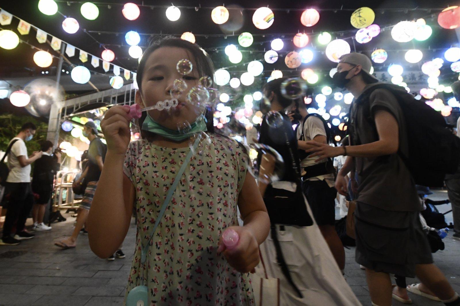 圖為兒童吹起泡泡于燈籠下玩樂。