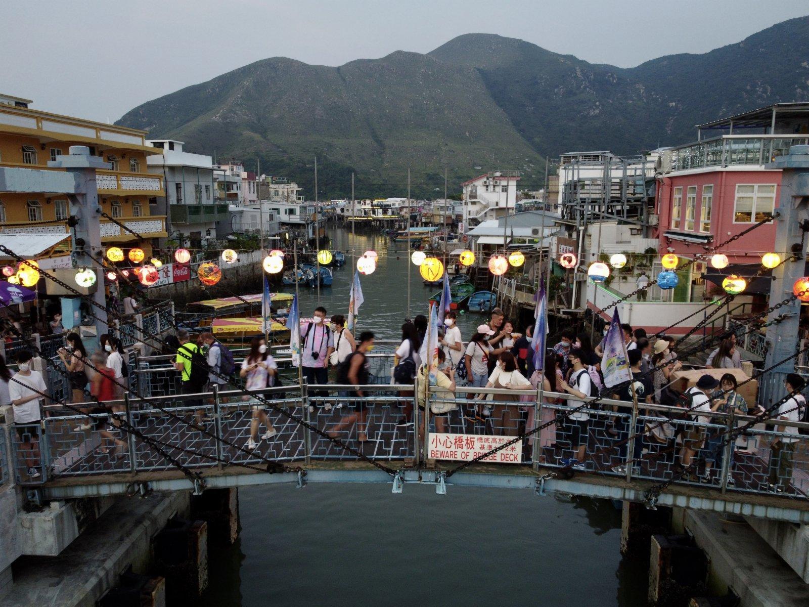 圖為市民走過掛滿燈籠的小橋。