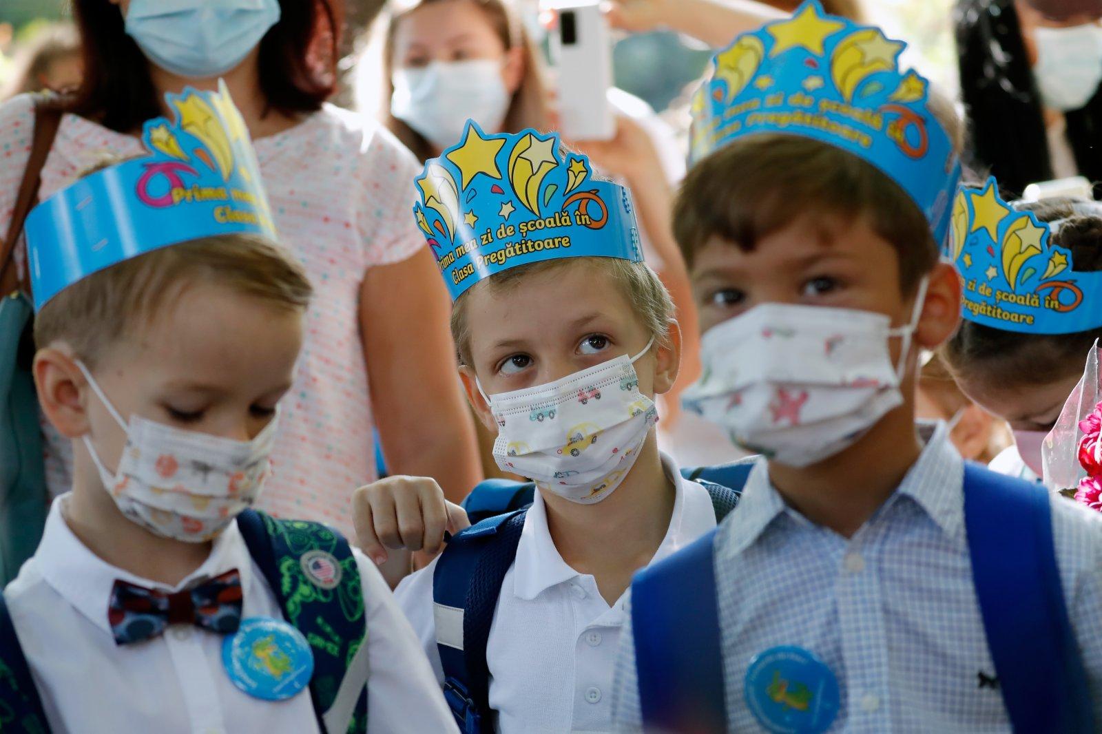 9月13日,在羅馬尼亞首都布加勒斯特,學生等待新學期開學典禮。當日,羅馬尼亞全國中小學開學,由於疫情日趨嚴重,政府要求所有人員必須戴口罩。(新華社)