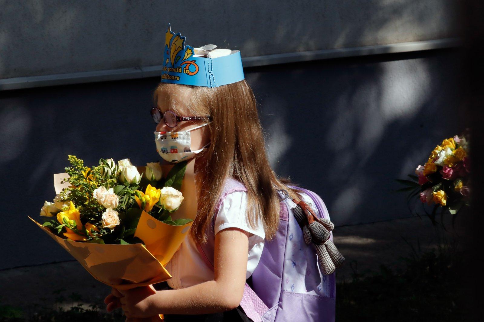 9月13日,在羅馬尼亞首都布加勒斯特,一名小學生進入學校參加新學期開學典禮。當日,羅馬尼亞全國中小學開學,由於疫情日趨嚴重,政府要求所有人員必須戴口罩。(新華社)