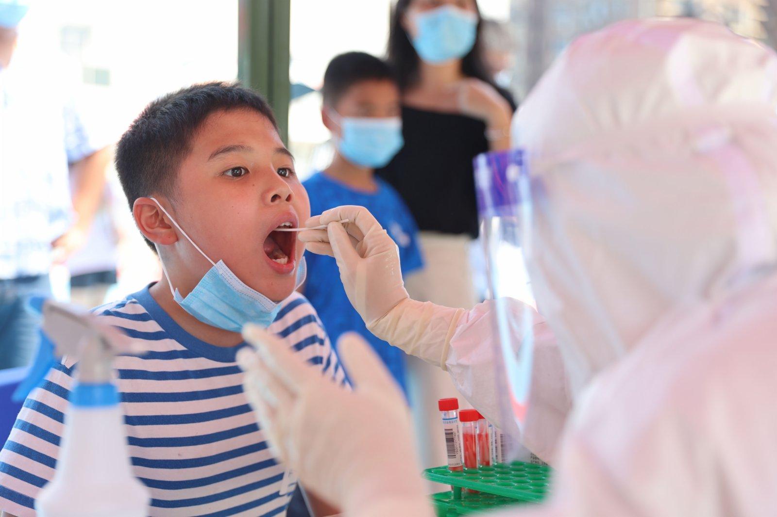 9月14日,在廈門市思明區篔簹街道金橋社區檢測點,醫務人員為小朋友進行核酸檢測採樣。(新華社)