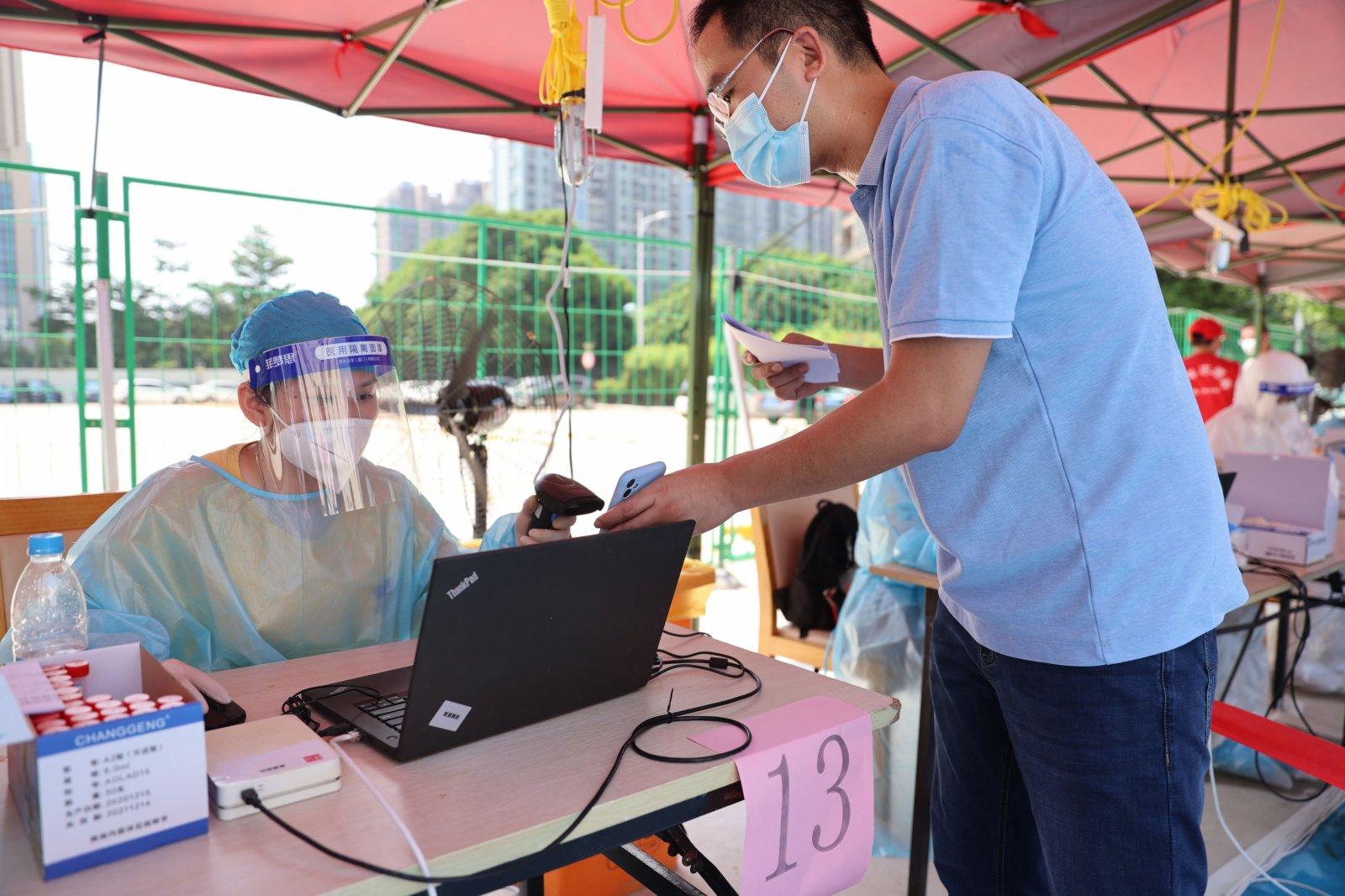 9月14日,在廈門市思明區篔簹街道金橋社區檢測點,工作人員為市民登記相關信息。(新華社)
