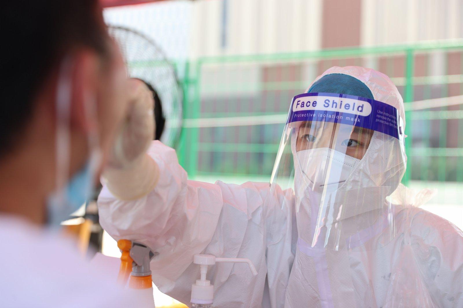 9月14日,在廈門市思明區篔簹街道金橋社區檢測點,醫務人員為市民進行核酸檢測採樣。(新華社)