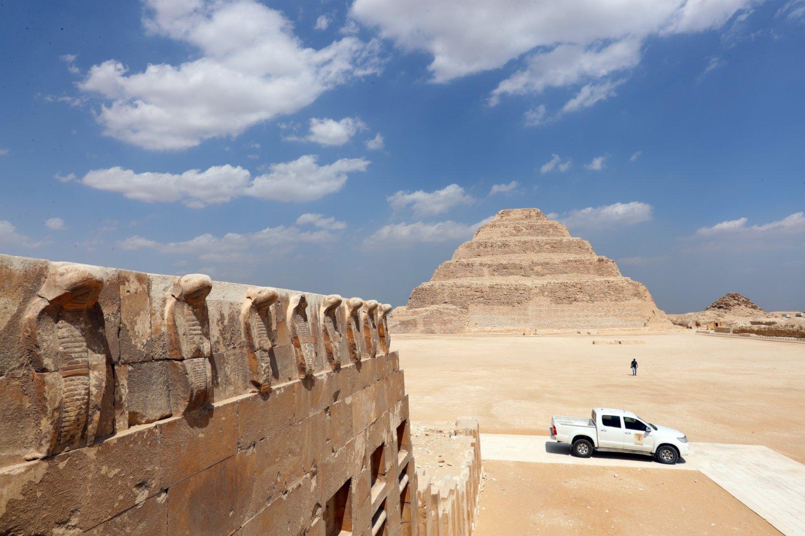 塞加拉地區一座左塞爾時期古墓地上建築的眼鏡蛇雕像,以及遠處的階梯金字塔。
