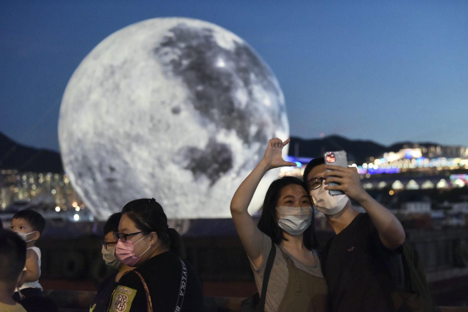 圖為市民與巨型「月亮」合影留念。(中新社)